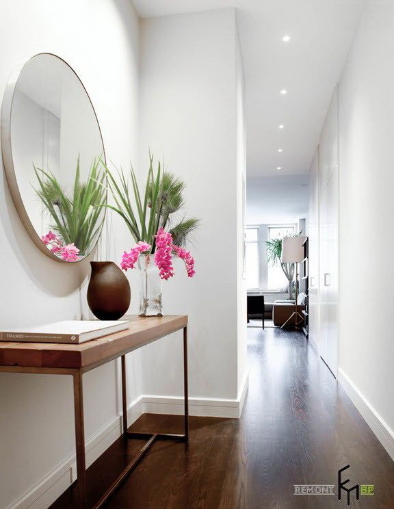 A Round Frameless Mirror For White Hallway With Hardwood Floor And