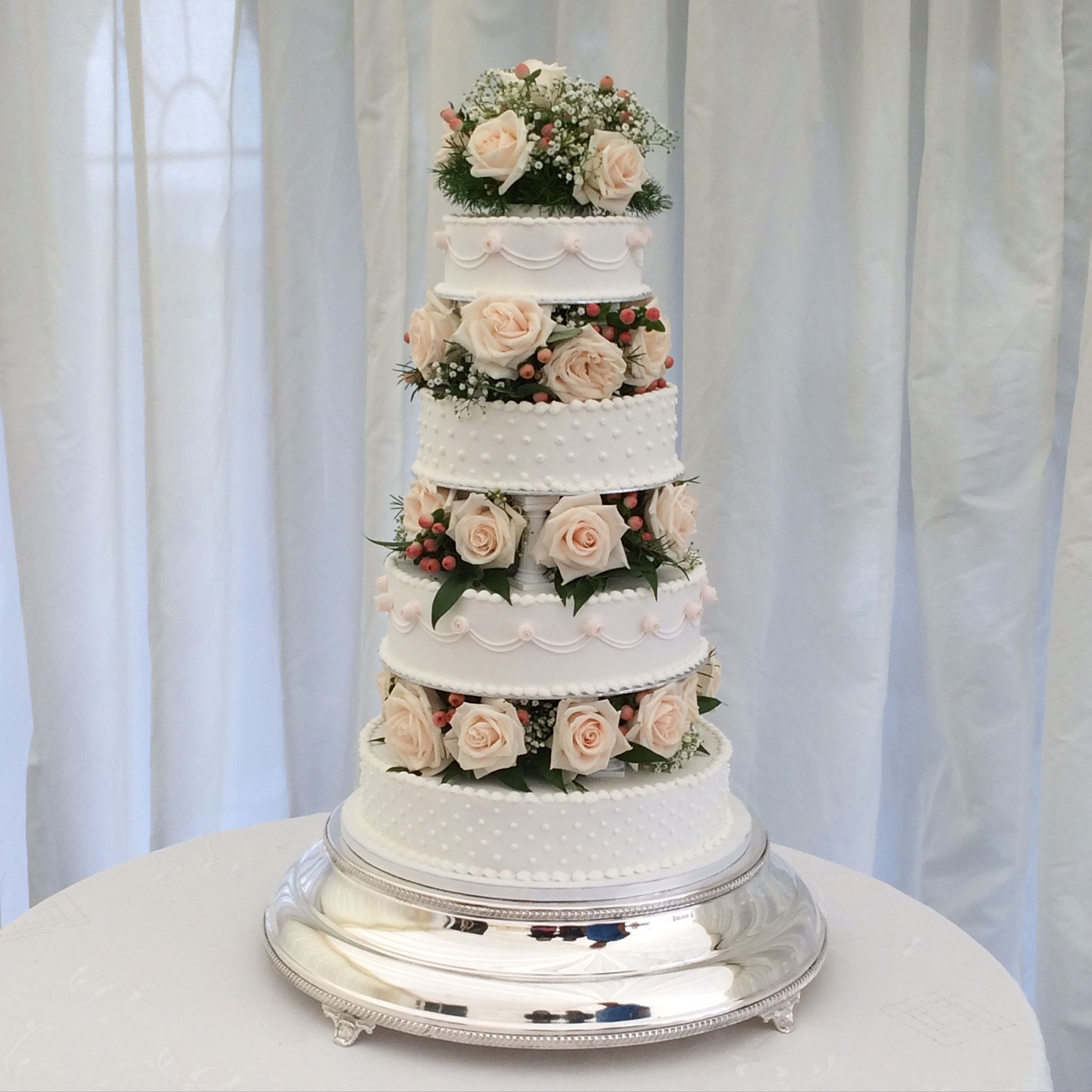 The wedding cake at the venue with fresh flowers between each layer ...