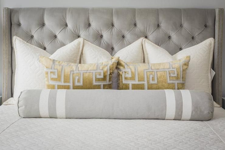 In Front Of A Gray Velvet Tufted Headboard Placed Against A Gray