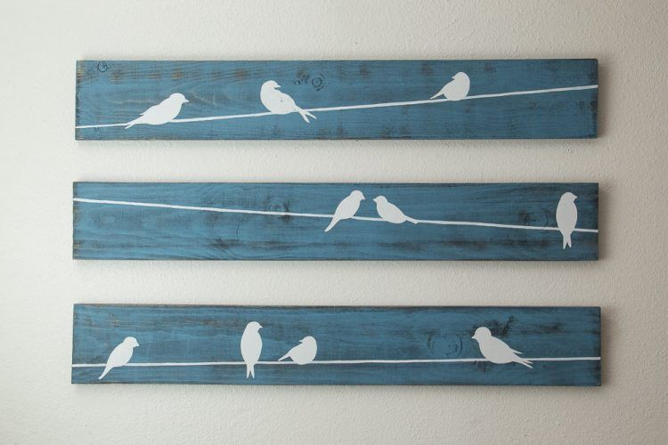 Adorable white birds on wire wall art design on mounted blue wooden boards on white wall