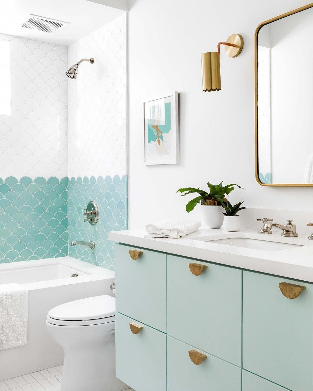 How fun is this bathroom? Yes, you can never go wrong with white, but the scalloped blue tile and drawer pulls give this room so much personality. We also love that it's a perfect match for our Bath Stone in Bora Bora Blue. #dorai #bathstone #bathroom #tiling #cabinets #goldaccessories #accessories #gold #blue #bath #doraihome #bathroomwallpaper
