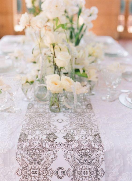 Un camino de mesa en blanco y gris de encaje y seda sobre un mantel blanco en Grand del Mar.