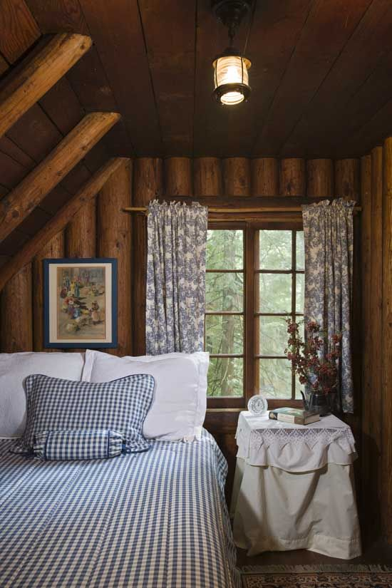 Now used as a guest room, one of the cabin's small bedrooms features  gorgeous vertically stacked, round-log walls, exposed log rafters and an  angled ...