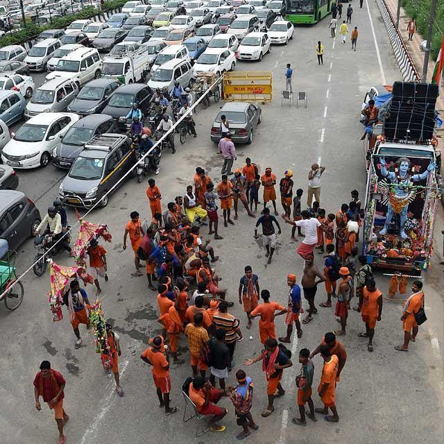 #Kanwarias devotees of God #Shiva take rest while others dance to religious songs at a rest-camp as #traffic crawls past in #Delhi. Kanwarias dressed in orange coloured clothes carry holy water (kanwar) of the river #Ganga from #Neelkanth #Gomukh or #Haridwar to be poured on the Shivlinga in their hometown temples on the occasion of #Shivratri. This journey on foot when completed is supposed to fulfil their wishes and endear them to Lord #Shiva. by ndtv