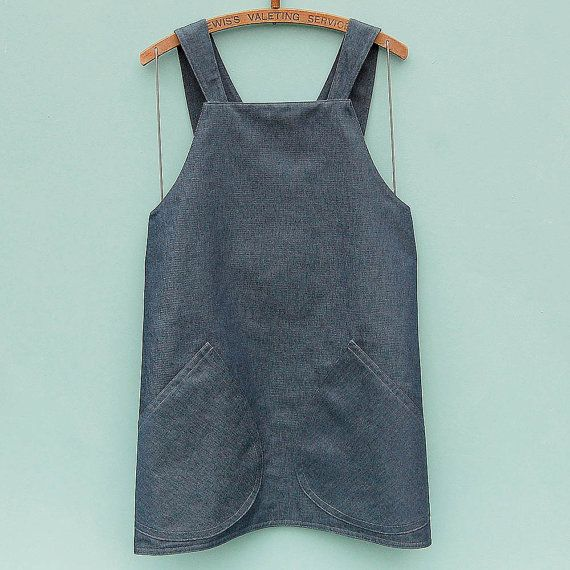 New shorter tunic top length version of ZUTusines denim Japanese apron made and fully lined with French indigo denim to create a super practical doubled denim reversible tunic apron dress. The crossover back apron style dress needs no ties to hold it in place; simply pop it over your head and the clever design holds itself securely around the body. This new design for 2016 has 2 large, rounded, patch pockets that have been double stiched for strength and detail, as have all the edges of the…