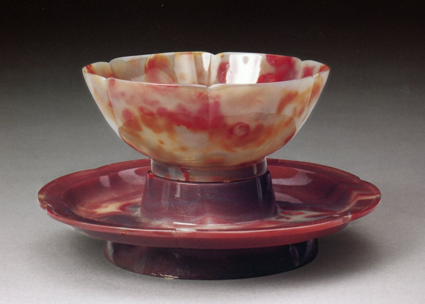 A cup and stem saucer base made from carved/polished red and cream-colored agate, Qianlong period (1736-1795 AD) Qing Dynasty. Overall Height: 8.5 cm; Cup Height: 4.7 cm; Diameter: 11.3 cm; Stem saucer Height: 2.7 cm. From the Forbidden City Palace collection.