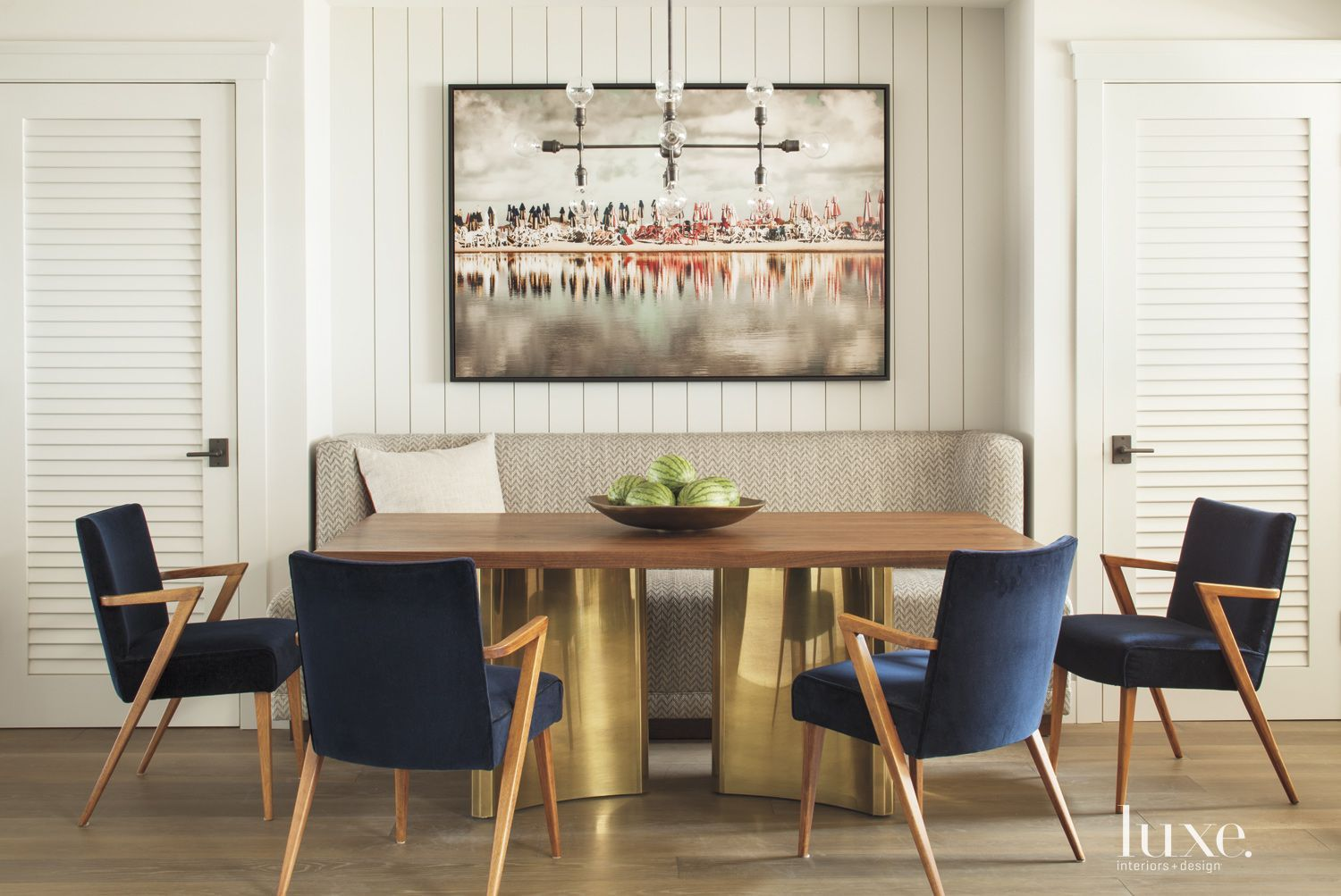 Massive brass base of the dining table brings a modern touch to this mid-century dining room furniture set.