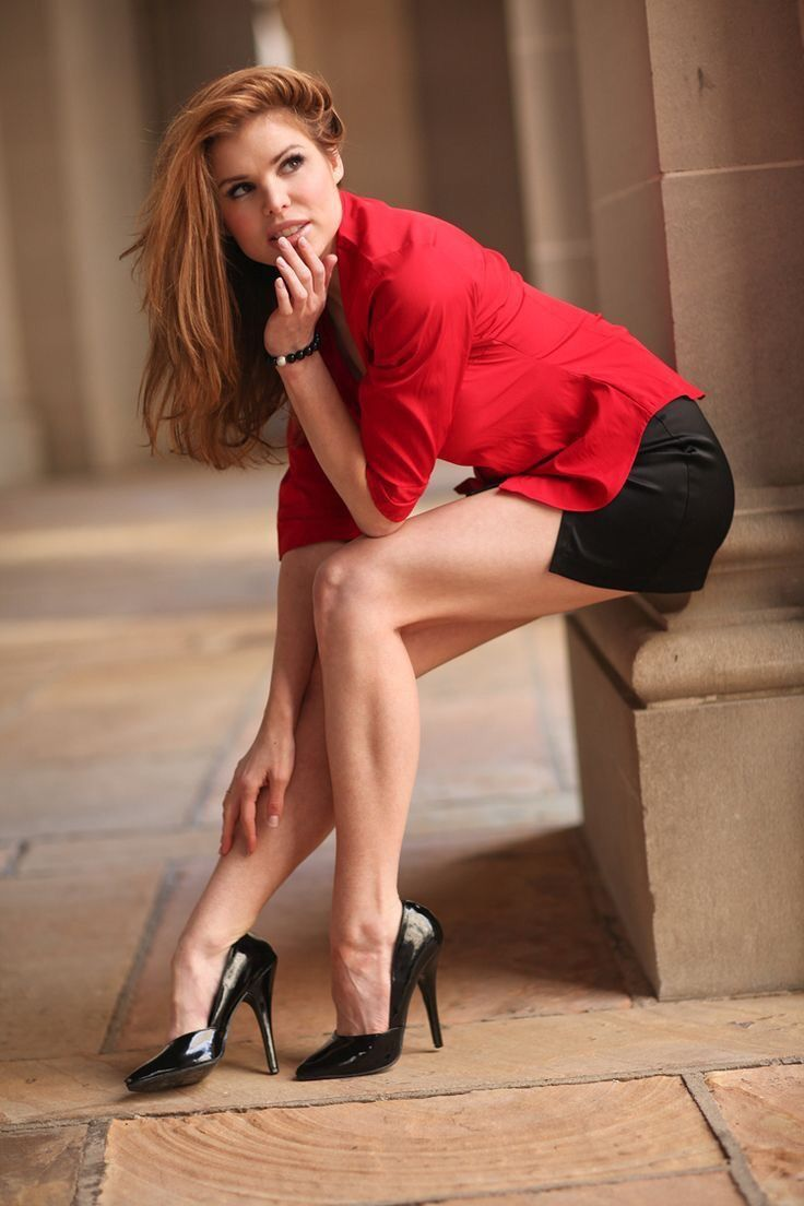 9cfbe666fb5a Lovely red head leggy in a short black mini skirt and black high heels  perched precariously on a stone column