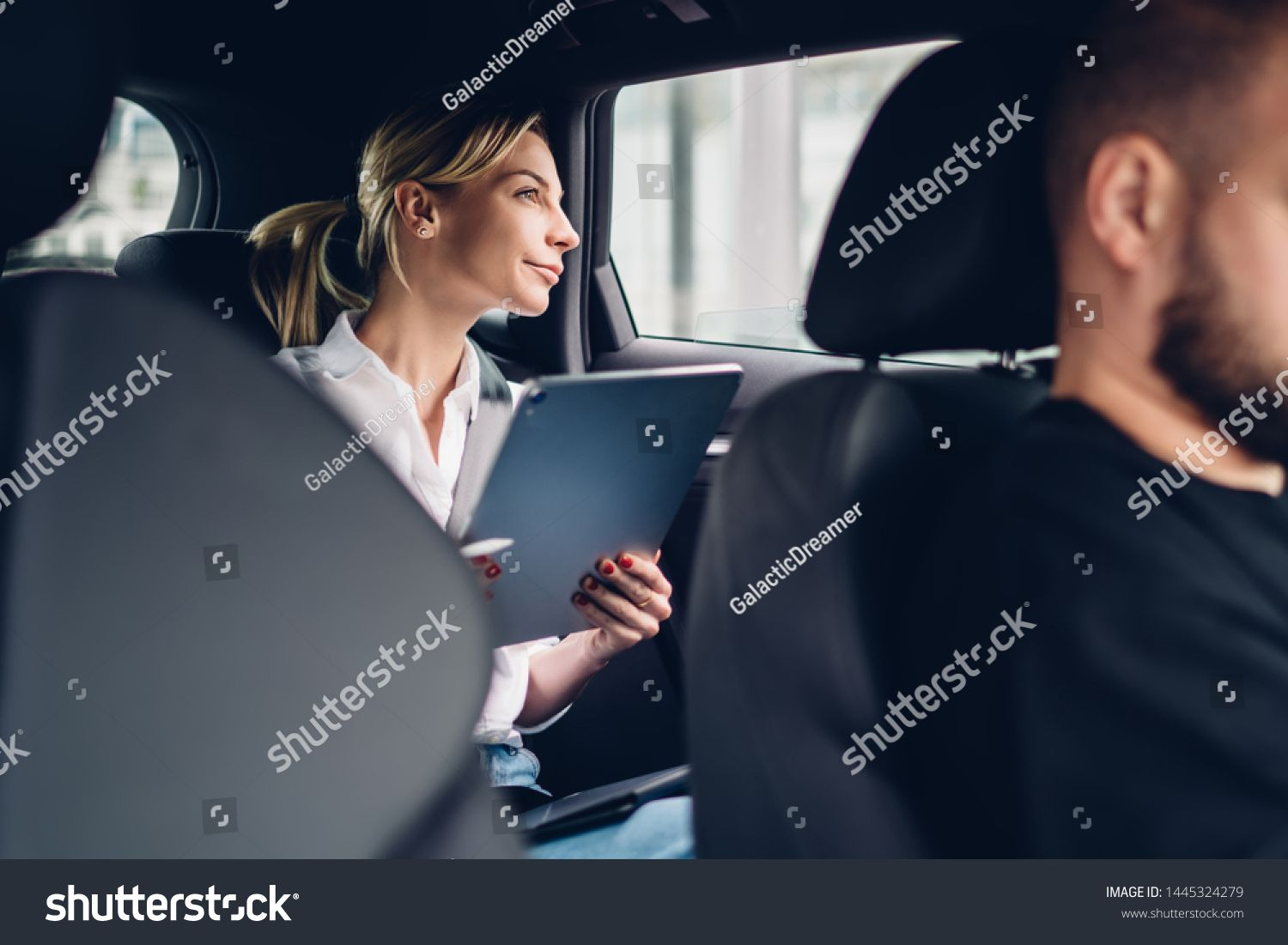 Pensive female passenger with portable tablet for remote