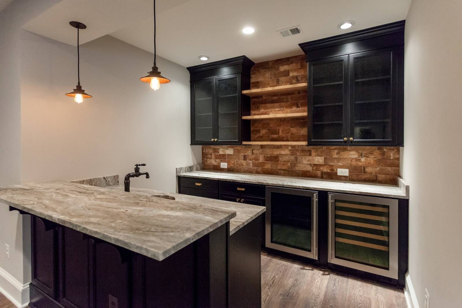 Basement Wet Bar With Black Lacquered Cabinets And Brick