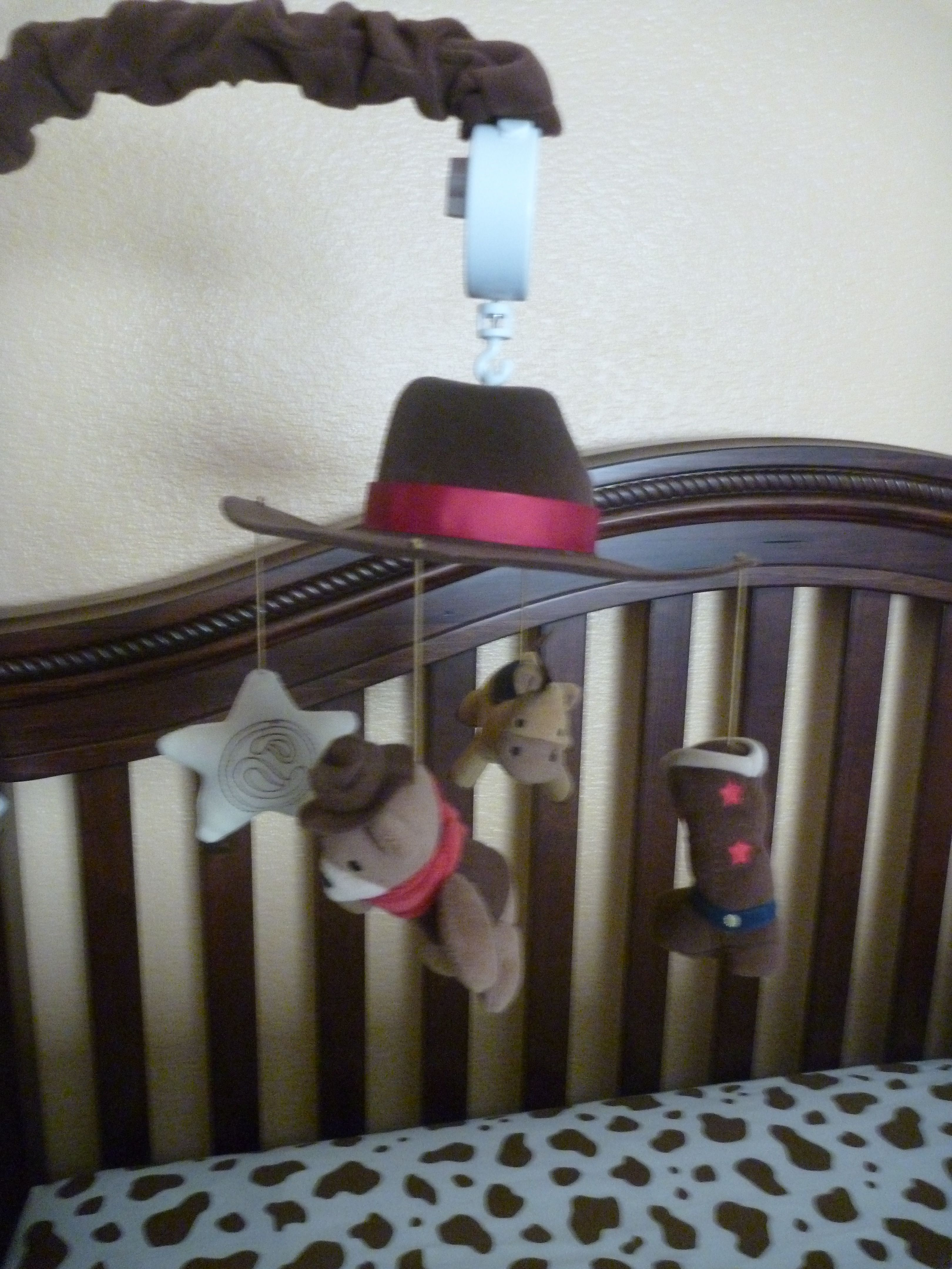 """""""Giddy Up"""" mobile. Consists of cowboy hat, western star, cowboy teddy, cowboy boot, and horse"""
