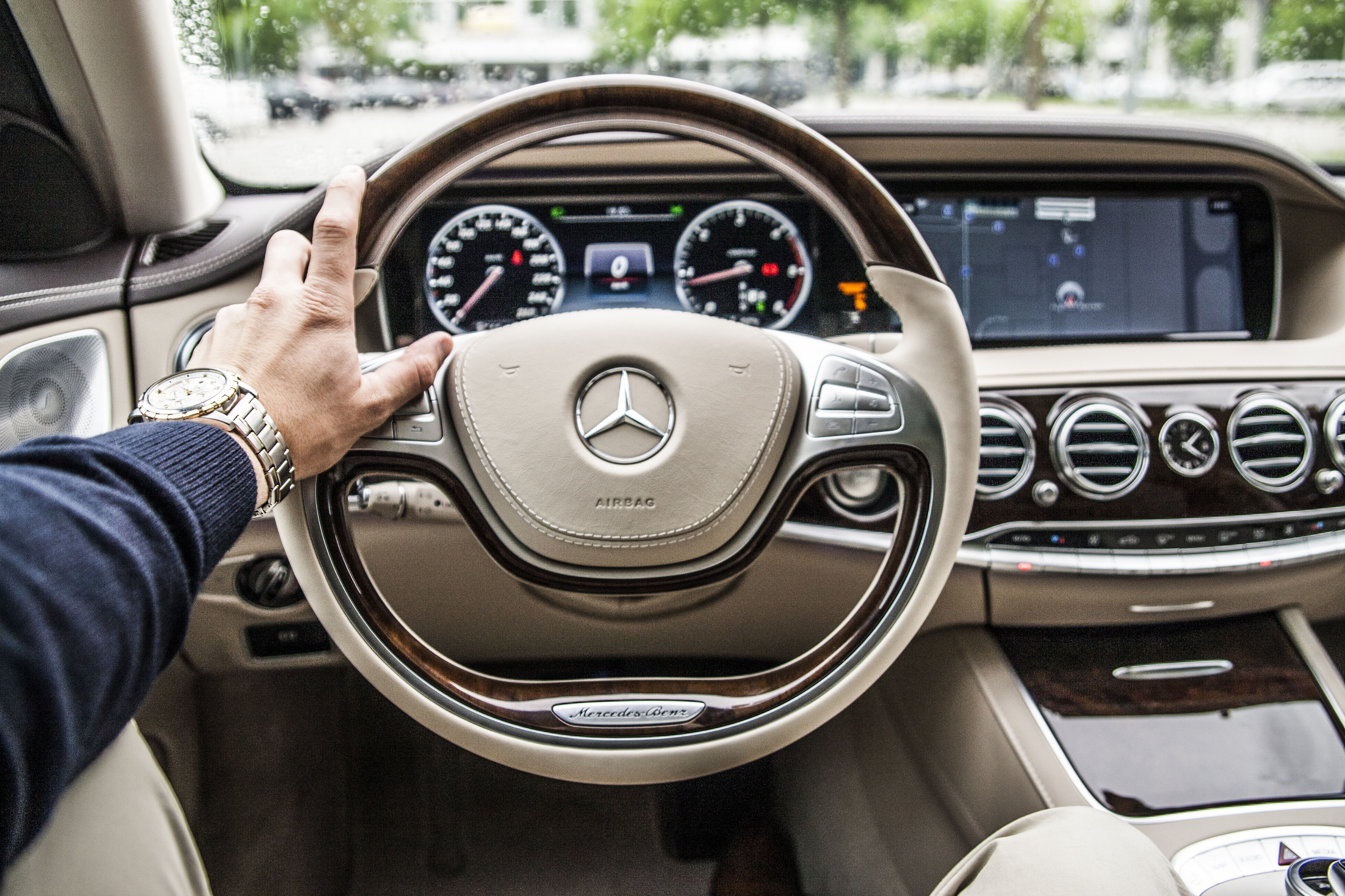 A Driver With His Hand On The Steering Wheel Of A Mercedes Benz