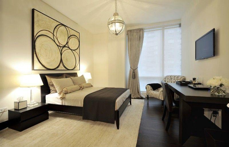 mid sized trendy guest dark wood floor bedroom with beige walls ...