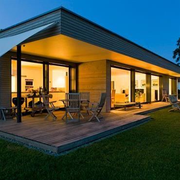 Villa en bardage bois avec toit plat et terrasse bois intégree