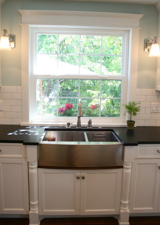 kitchen sink window overlooking deck with white kitchen cabinets white marble countertop and stainless steel apron sink