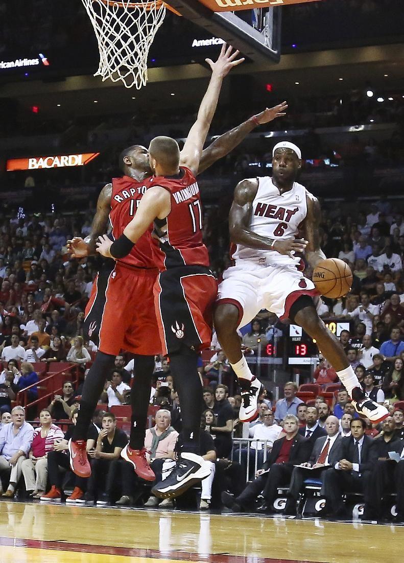 Toronto Raptors Defenders Amir Johnson 15 And Jonas Valanciunas 17 Try To Block Miami Heat S Lebron James 6 F Nba Basketball Game Lebron James Miami Heat