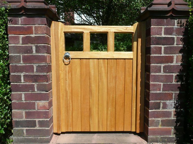 Ein Gartentor aus Holz sorgt für Abwechslung in einer Backsteinmauer ...