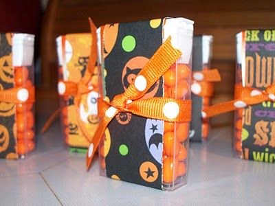 """Tic Tac - green, of course. Cut scrapbook paper into 1.25"""" x 7.5"""" strips and wrap them vertically around orange tic-tac containers securing with adhesive.  Then wrap some decorative ribbon horizontally around the tic-tac containers and tie in a knot."""