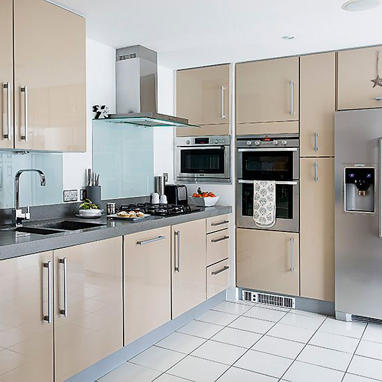 Pale modern kitchen units with glass splashbacks and white tiled ...