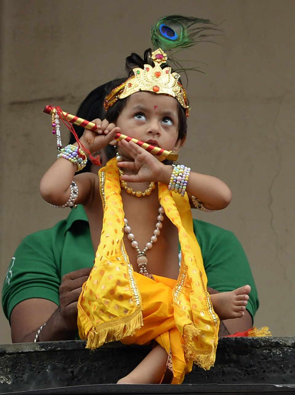 5899d5910 An Indian child dressed as Hindu god Lord Krishna looks on during ...