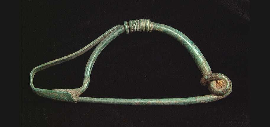 """CHOICE GREEK BRONZE FIBULA. Hellenistic, c. 2nd century BC. The bow-type fibula with tail extending past the catch plate where it is turned back and wrapped around the body, the head wrapped round itself to form a spring terminating in the pin which rests in the catch plate, the whole with a superb beautiful sea-green patina. 2.85"""""""