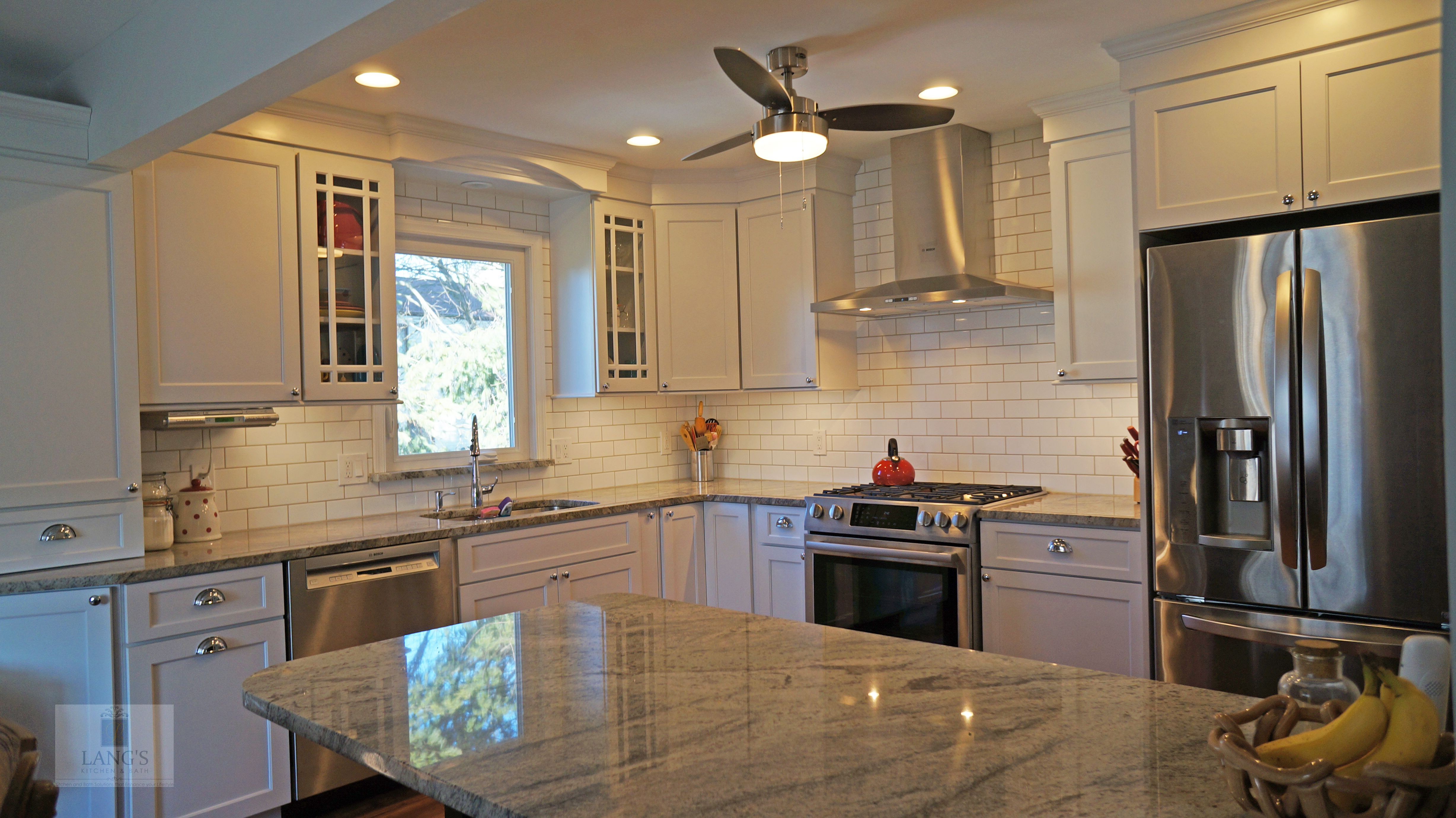 The white Koch kitchen cabinets accented by a dark wood ...