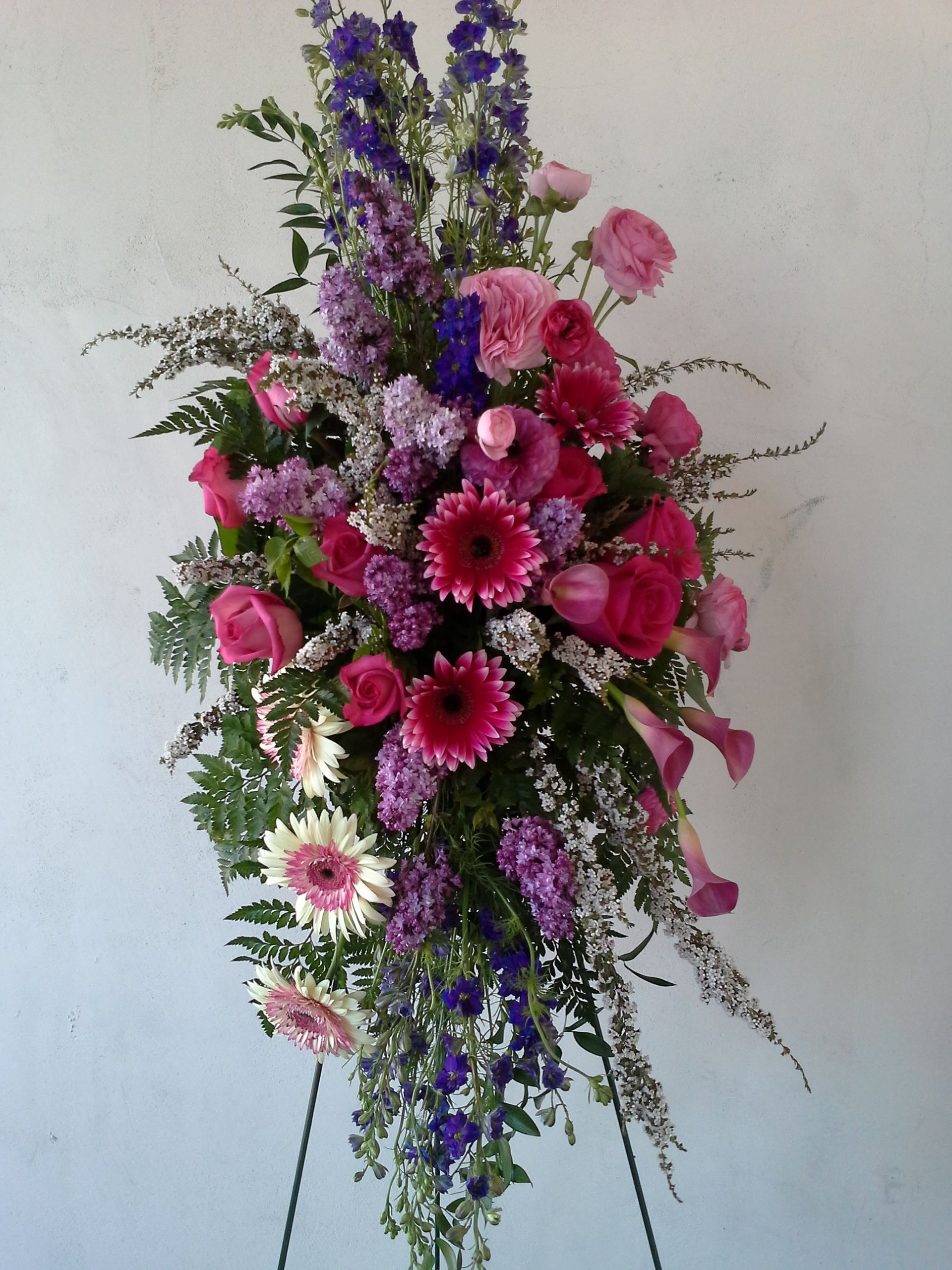 Standing funeral spray of stargazer lilies blue delphinium purple funeral spray in purples lavender and pinks izmirmasajfo
