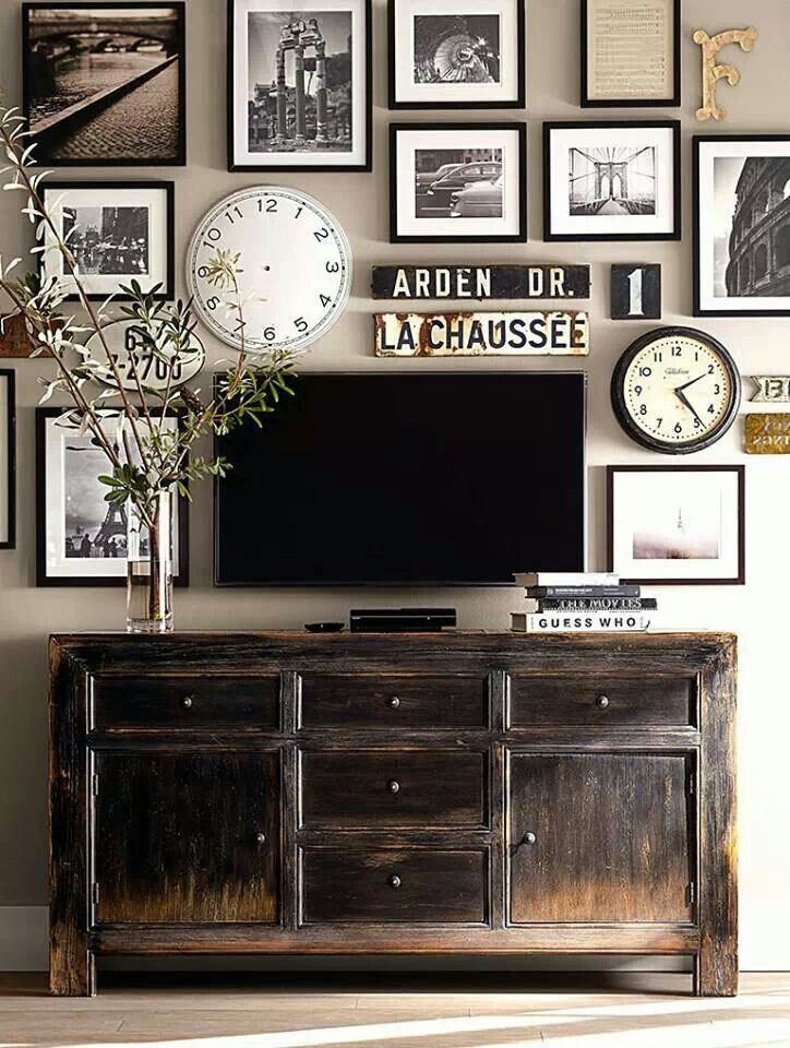 Distressed wood cabinet + melange of framed prints & collectibles = camouflaging the screen....well done!