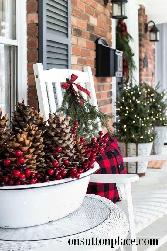 White metal bowl and buckets with Christmas decor on front porch