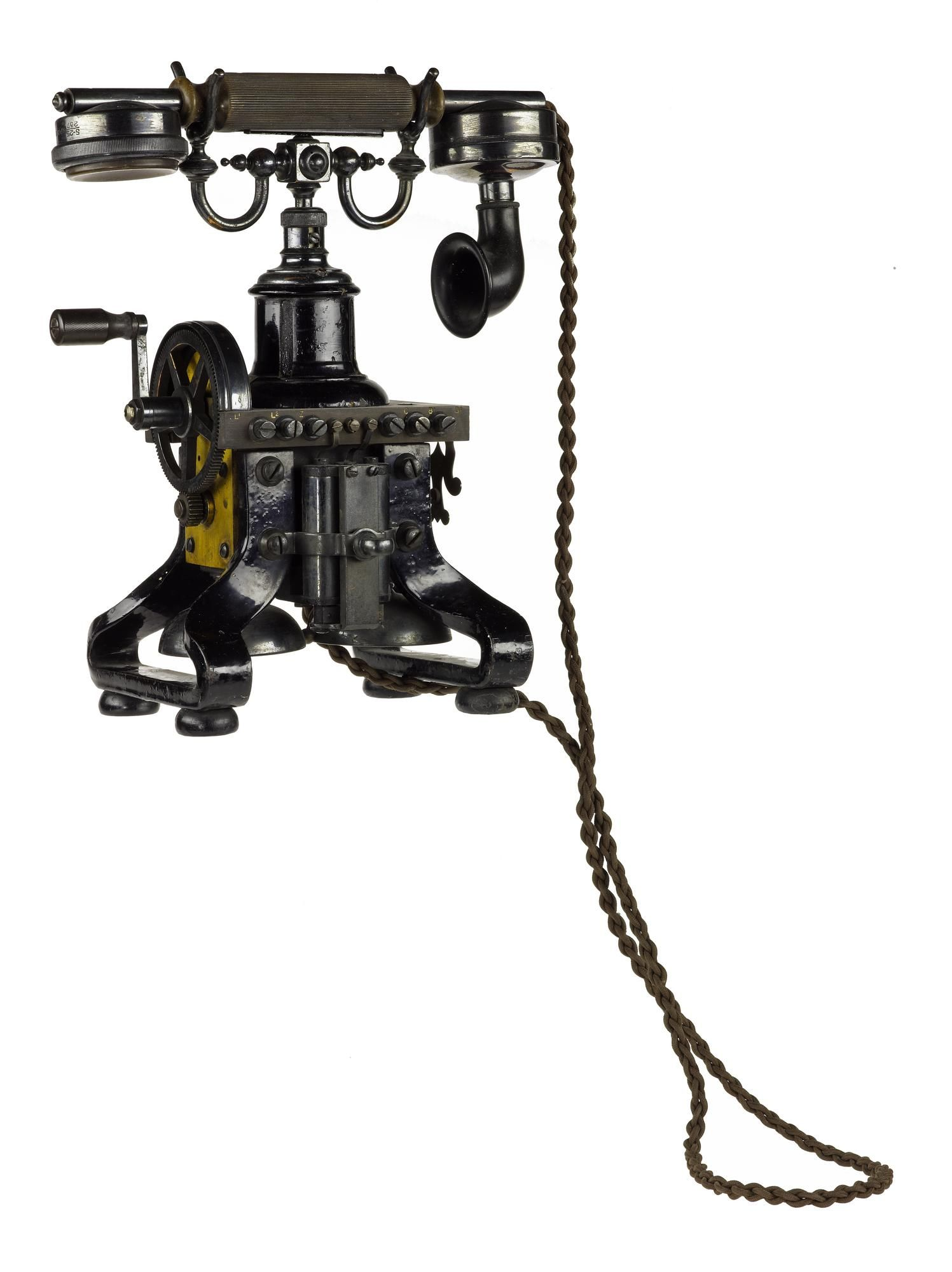 Hand telephone set, c. 1900, with the handset on a cradle above the instrument which rests on the magnets of the magneto generator, and designed for table mounting.