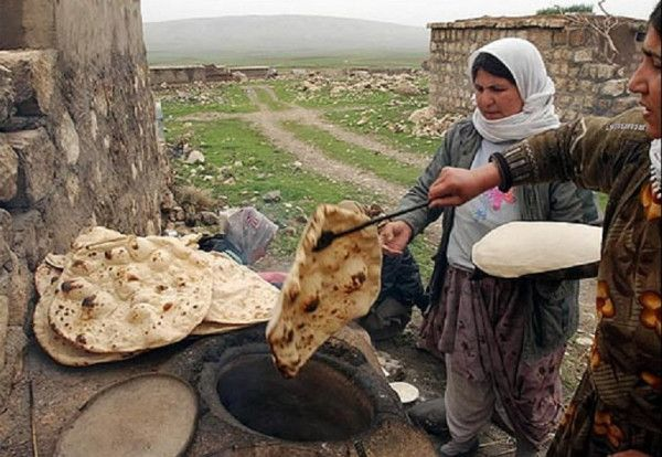 'Kurdish women from the village of Sina make fresh bread in Kurdish-ruled northern Iraq, march 26, 2003', AP Photo