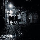 Silhouette of Group Walking Through Alley at Night