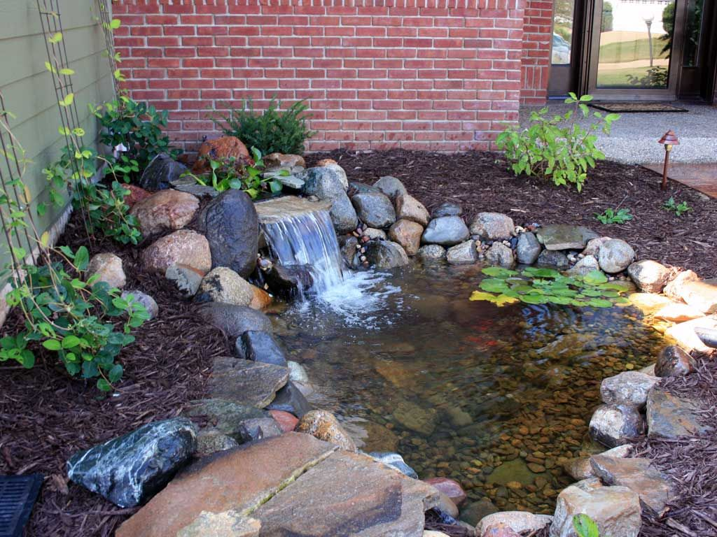 Backyard waterfall with pond minnesota waterfeatures for Outside fish pond ideas