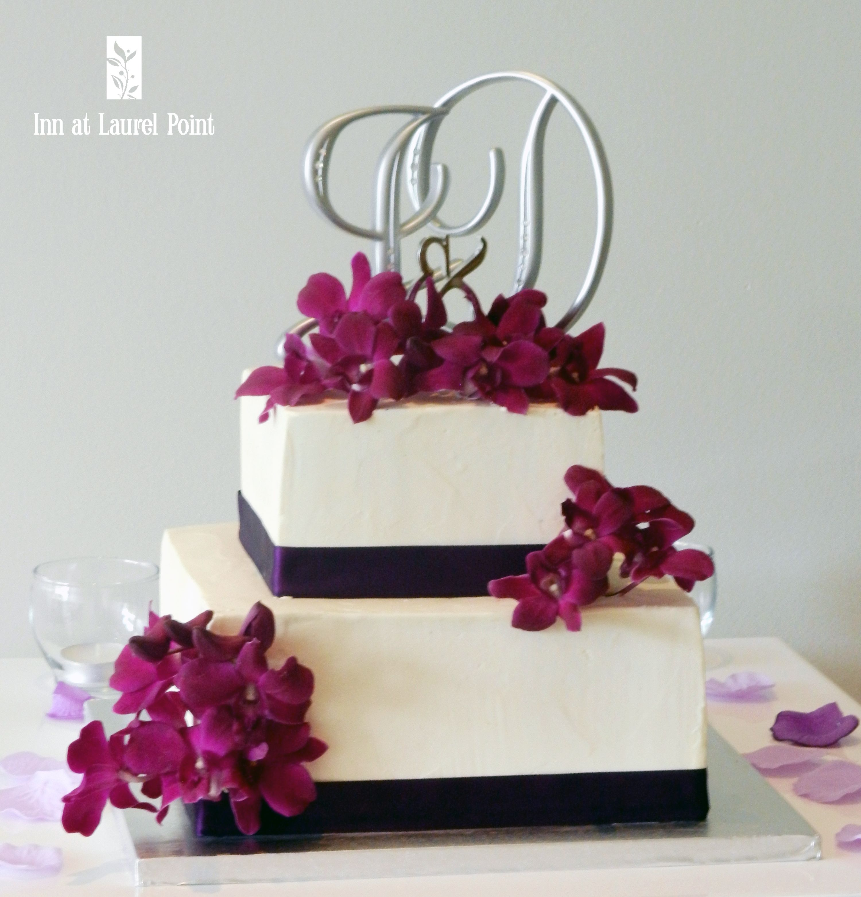 Two tier wedding cake with orchids and a monogram topper tier