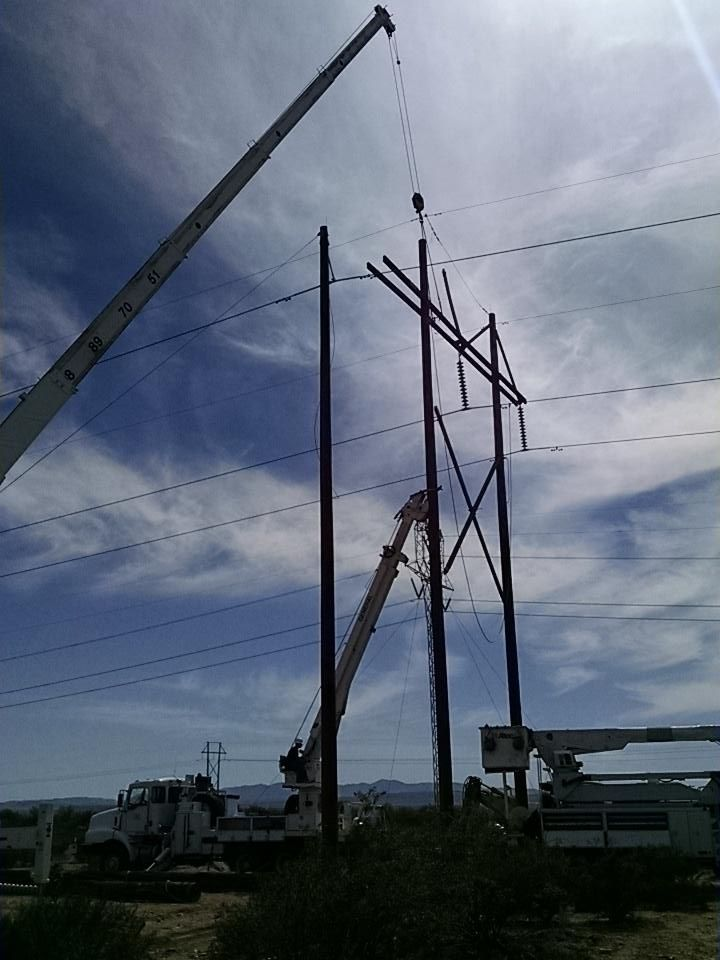 Crews pin a replacement pole to the supports that connect