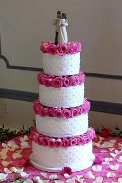 Four tier white and pink wedding cake garnished with pink roses four tier white and pink wedding cake garnished with pink roses mightylinksfo