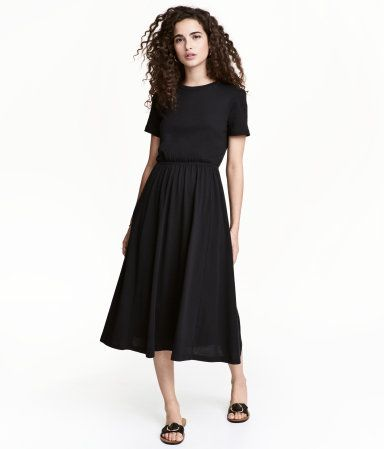 80f059d018 Black. Knee-length, short-sleeved dress in cotton jersey. Cut-out section  at back with snap fasteners at top. Elasticized seam at waist and circle  skirt.
