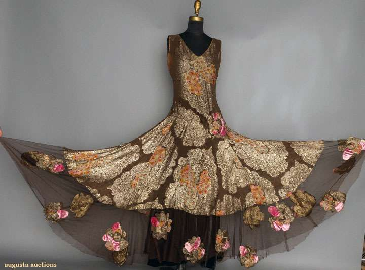 1930 Chocolate brown silk brocaded in gold lame cartouches w/ printed orange & pink blossoms, net hem edge w/ printed lame appliques. Detail