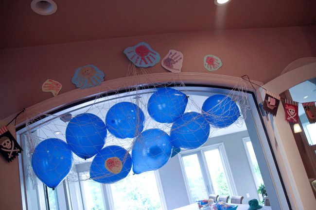 Under the Sea party- Blue balloons, netting, and handprint fish. Balloon drop.