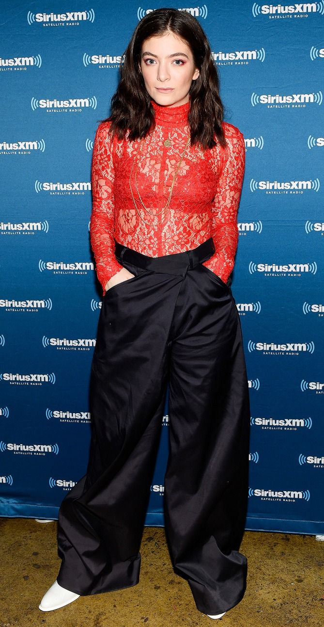 Lorde in a red sheer lace top and wide-leg black pants