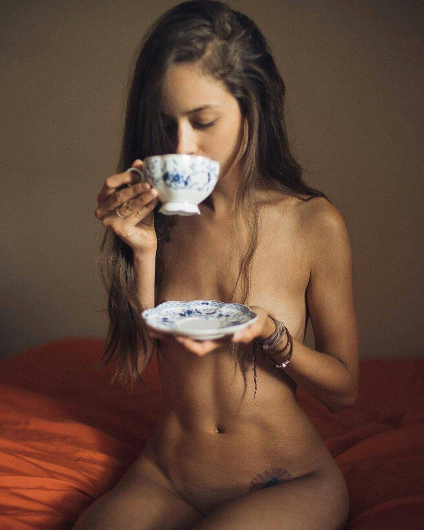 Attractive beautiful half naked woman drinking coffee on the sofa stock photo