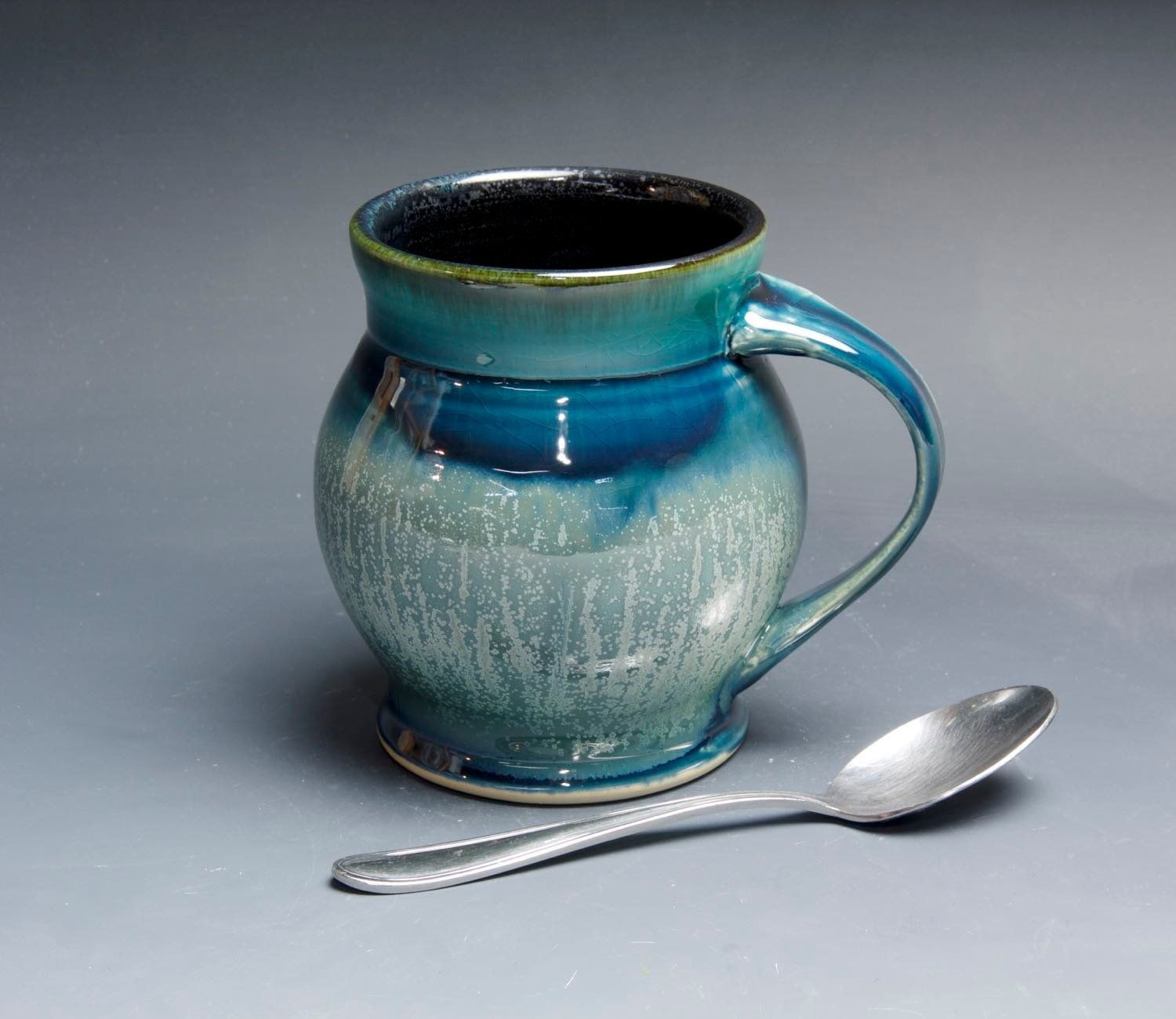 Thick silvery accents on this mug. 20 ounces. With blue green near the lip and black liner glaze ...