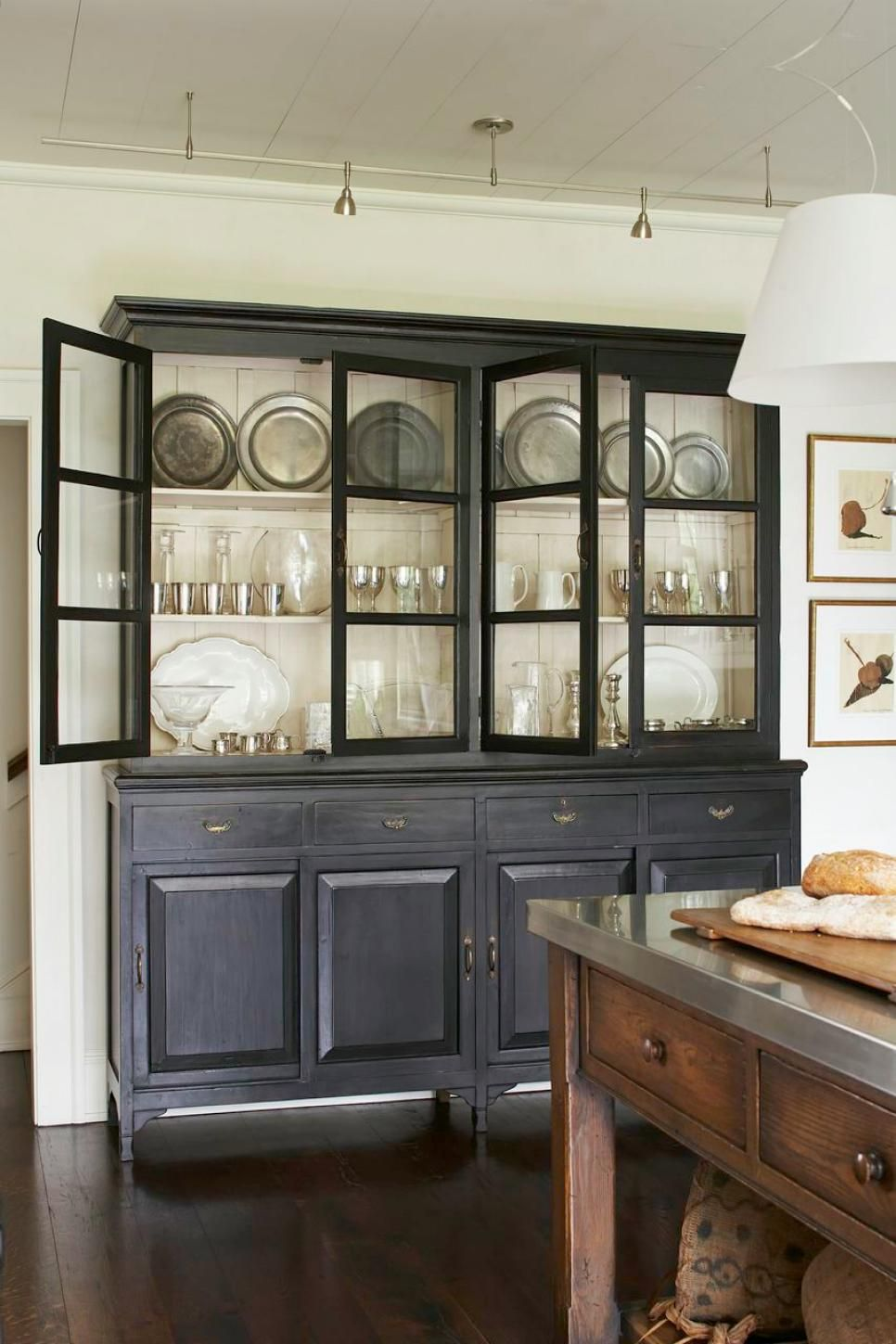 Painted black cabinetry with glass fronts backed with wide white ...