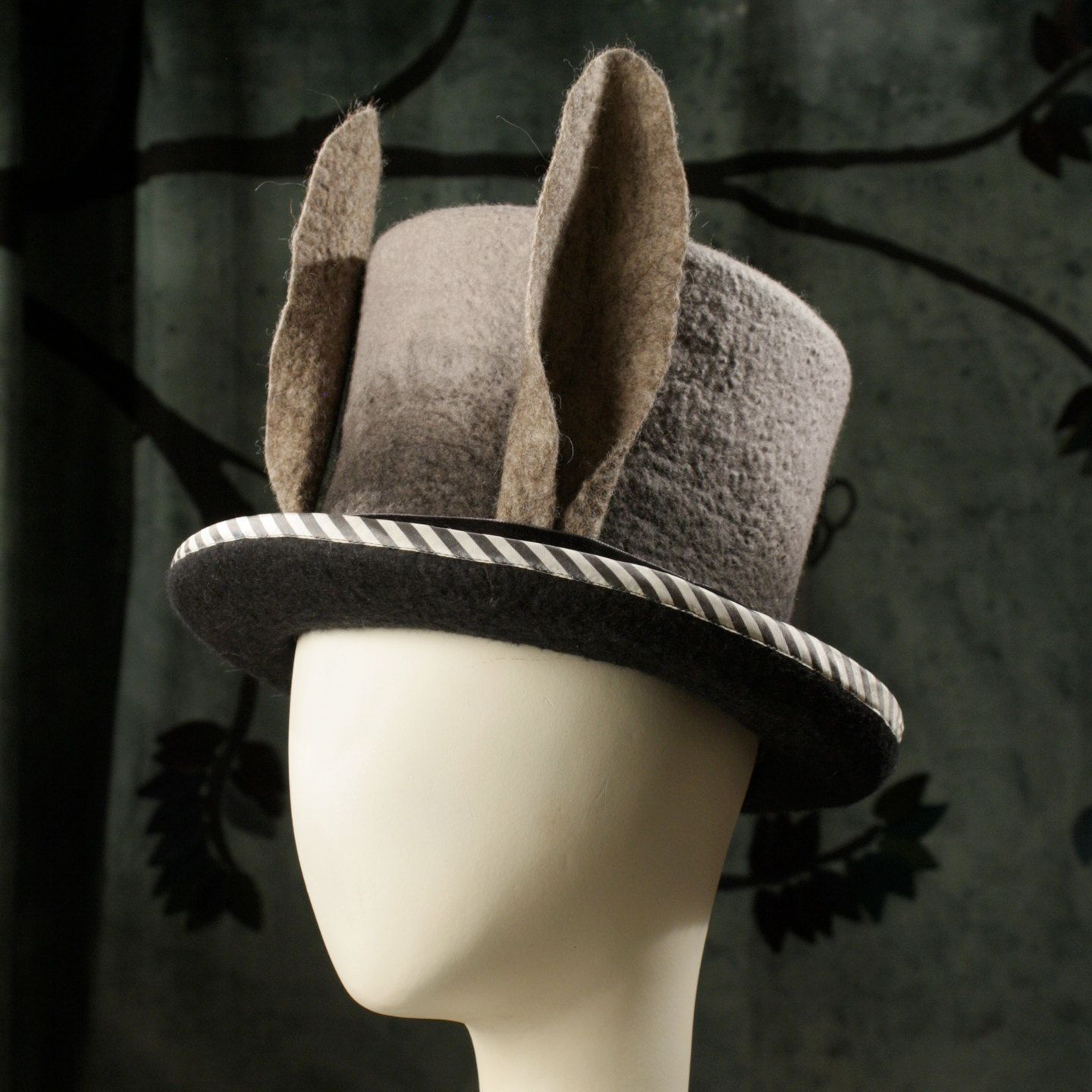 c9bc1ba0a317a An ombre black to white top hat with large rabbit ears. The crown is  encircled with a black velvet ribbon and finished at the side with a brass  stamped key ...