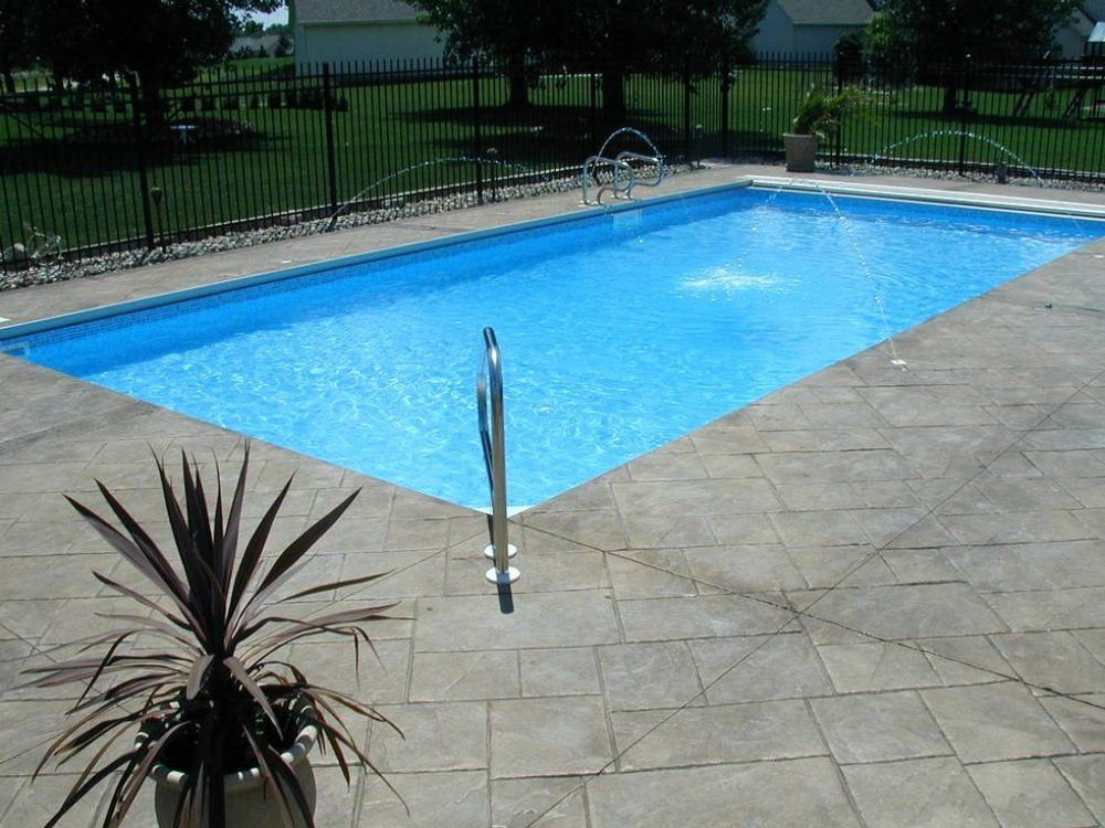 Here's a traditional rectangular inground pool with a ...