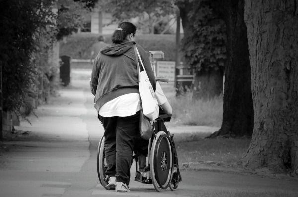 Foto de mamá impulsando hijo en silla de ruedas