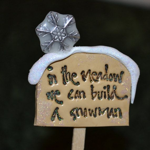 This listing is for one sign that reads, in the meadow we can build a snowman. The sign is made of polymer clay and wood, glitter and paint,
