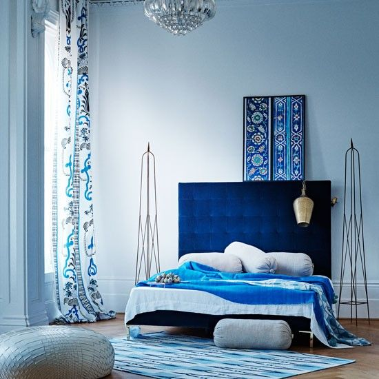 Contemporary blue bedroom with low-level bed and patterned curtain ...