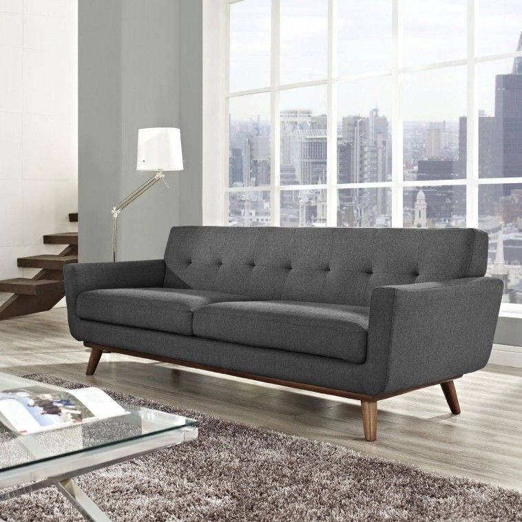 Grey Fabric Couch With Back And Arms Also Brown Wooden Legs On The Floor Connected By Glass Windows And Grey Wall