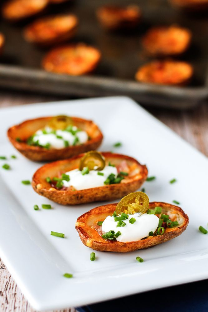 How To Make Potato Skins -- crispy, cheesy loaded potato skins are the ultimate homegating party appetizer. Topped with bacon, sour cream, chives and an optional jalapeno pepper, they're sure to please!